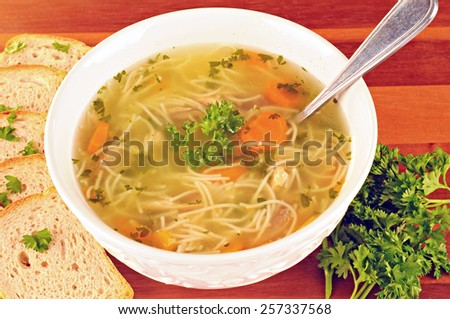Bowl with chicken soup with vegetables and chicken meat, toasted bread, spoon, on wooden table