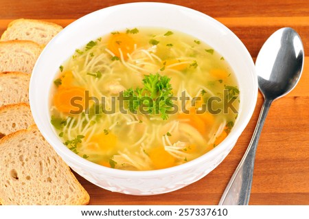 Bowl with chicken soup with vegetables and chicken meat, toasted bread, spoon, on wooden table  - stock photo