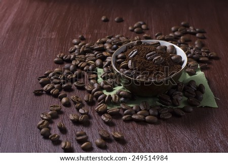 Bowl with coffee beans and ground coffee on a dark photo - stock photo