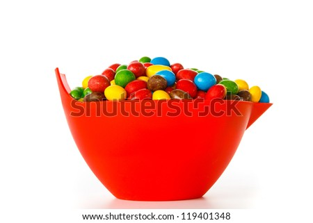 Bowl with colorful chocolate sweets against white background - stock photo