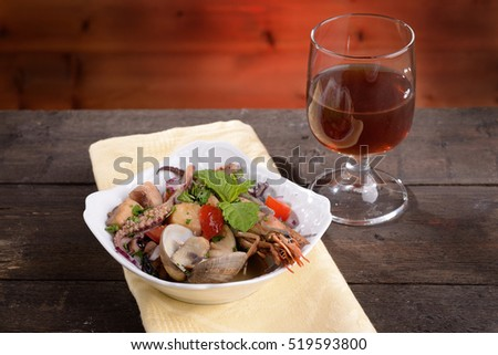 Bowl with dressing Mixed seafood and glass of wine