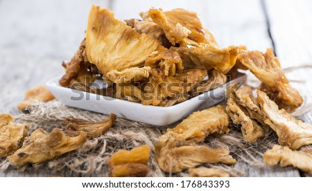 Bowl with dried Pineapple on wooden background