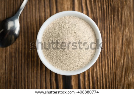 Bowl with dried Yeast (selective focus) on wooden background - stock photo