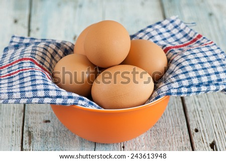 Bowl with eggs and dish towel on old wooden table