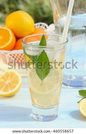 Bowl with fresh orange and lemon and glass of lemonade with fresh mint on blue wooden background