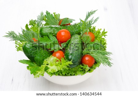 bowl with fresh vegetables for salad on white background