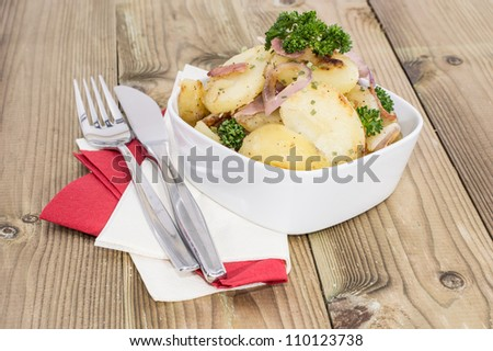 Bowl with fried Potatoes on wooden background - stock photo