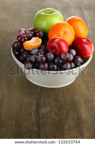 Bowl with fruits, on wooden table - stock photo