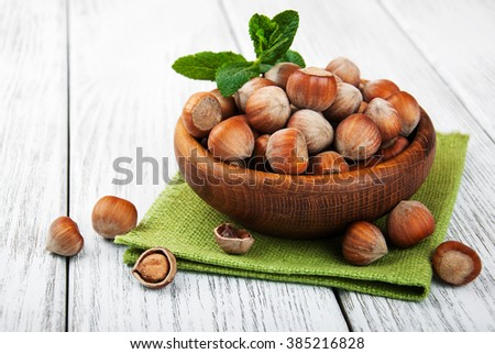 Bowl with hazelnuts on a old wooden table - stock photo