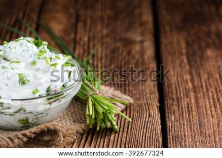 Bowl with Herb Curd (detailed close-up shot) on wooden background - stock photo