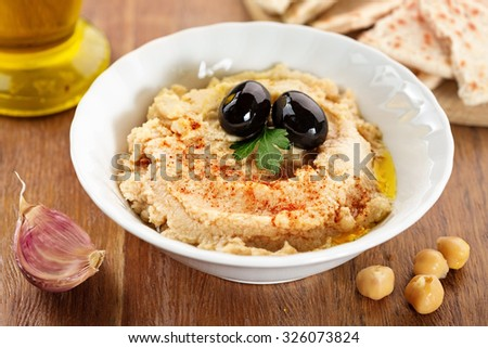 bowl with hummus, garlic and chickpeas on wooden table - stock photo