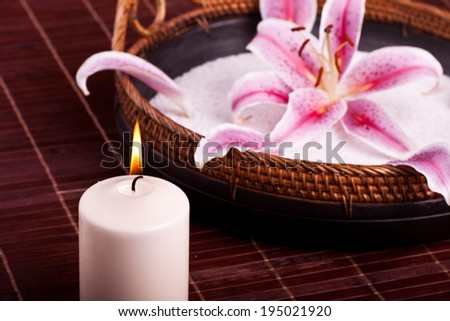 Bowl with lily and candle - stock photo
