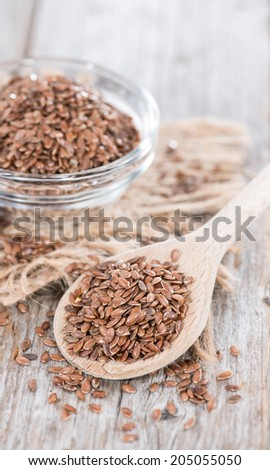 Bowl with Linseeds (close-up shot) on vintage wooden background - stock photo