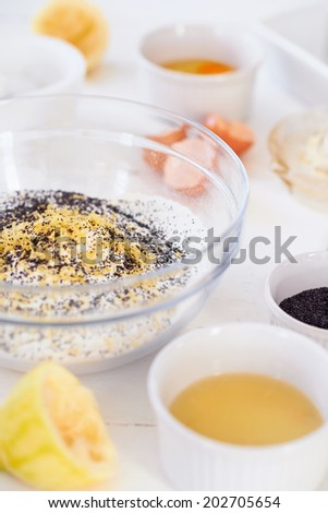 Bowl with mixture of poppy seeds, flour, and lemon zest with egg and lemon ingredients next to it - stock photo