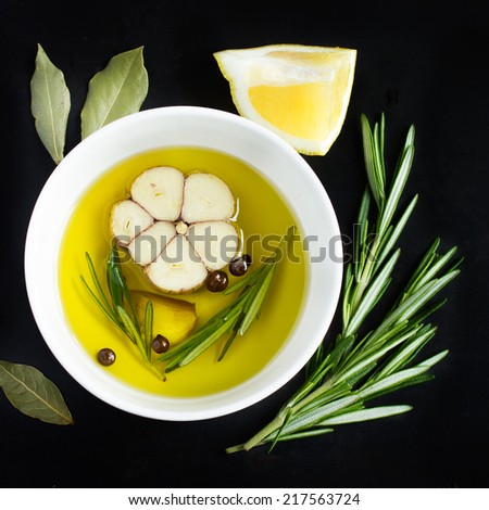 bowl with olive oil, garlic, peppercorn, lemon   and rosemary on a black background, top view, square image - stock photo