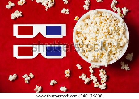 bowl with popcorn and 3D glasses on red background. mock up. top view. - stock photo