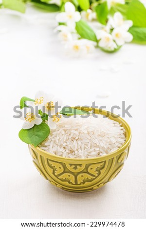 Bowl with rice jasmine  and jasmine flower - stock photo