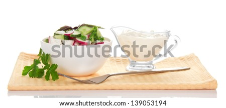 Bowl with salad, a cup with sour cream and a fork on a napkin, isolated on white