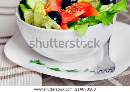 Bowl with salad on table - stock photo