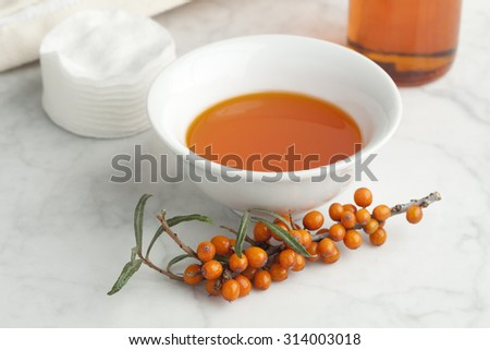 Bowl with Sea buckthorn oil  with a twig of common sea-buckthorn  - stock photo