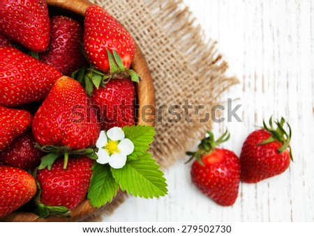 Bowl with strawberries on a old wooden background - stock photo
