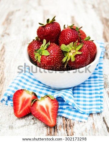 Bowl with strawberries on a old wooden background