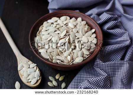 Bowl with toasted pumpkin seeds, wooden spoon - stock photo