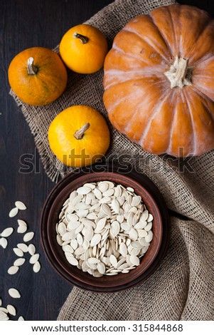 Bowl with toasted pumpkin seeds, wooden spoon
