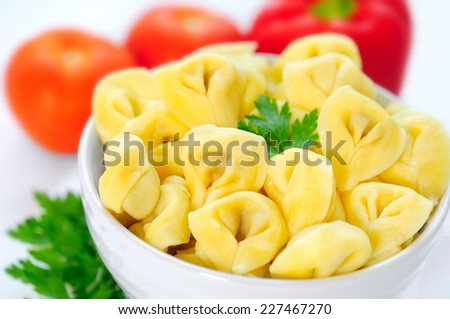 Bowl with tortellini on background - stock photo