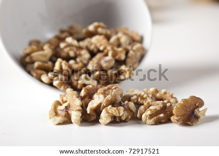Bowl with walnuts on a white table - stock photo