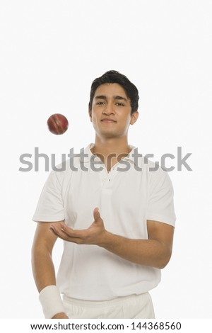 Bowler tossing a cricket ball - stock photo