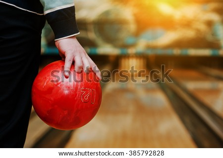 Bowling ball at hand of man background bowling alley - stock photo