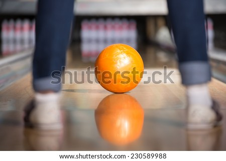 Bowling ball is rolling down the path to the bowling pins.