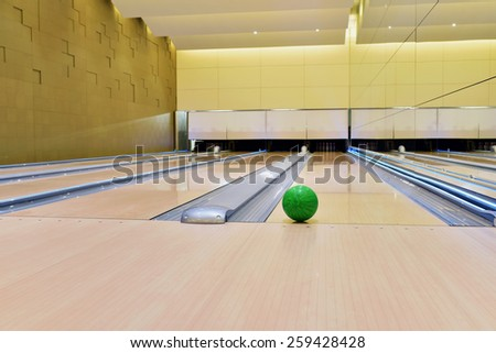 Bowling ball lying on bowling alley It will be strike. Green bowling ball rolling along bowling alley - stock photo