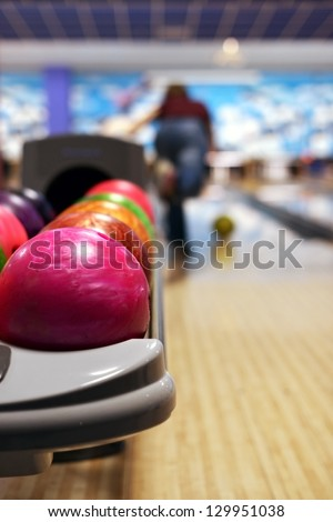 Bowling ball machine with person bowling in the background - stock photo