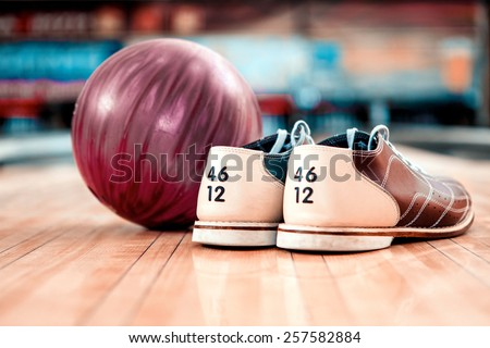 Bowling equipment. Close up of bowling shoes and lilac ball lying on bowling alley - stock photo