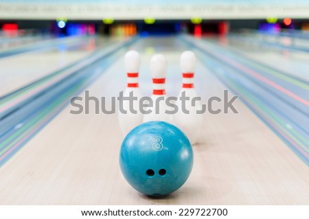 Bowling game. Close-up of blue bowling ball lying against pins staying on bowling alley   - stock photo