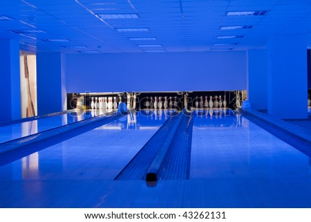 Bowling hall. Bowling bowls in row. View of the bowling rolling lanes at a local club. - stock photo