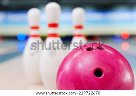 Bowling in details. Close-up of red bowling ball lying against pins staying on bowling alley   - stock photo