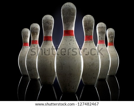 Bowling pins illuminated over black background