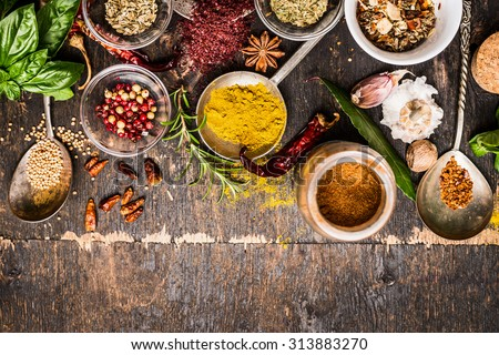 Bowls and spoon of  Various spices selection on rustic wooden background, top view, border