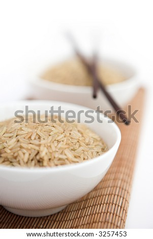 Bowls of brown rice & chopsticks on top of a bamboo mat - shallow dof - stock photo