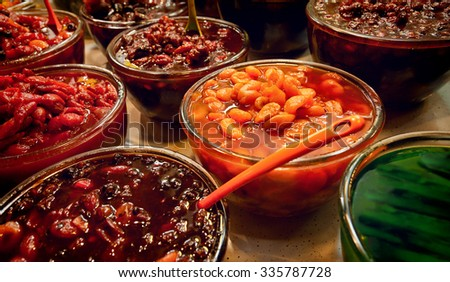 Bowls of colorful pickled fruits in vinegar that are served as tasteful sides with Iranian food. - stock photo
