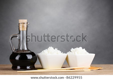 Bowls of cooked rice and soy sauce in jar on wooden table on gray background - stock photo