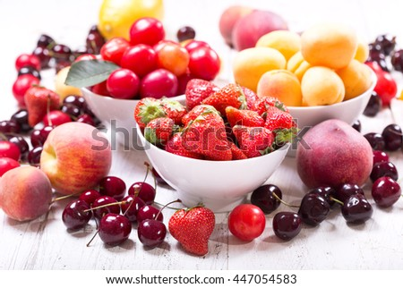 bowls of fresh fruits and berries on wooden table