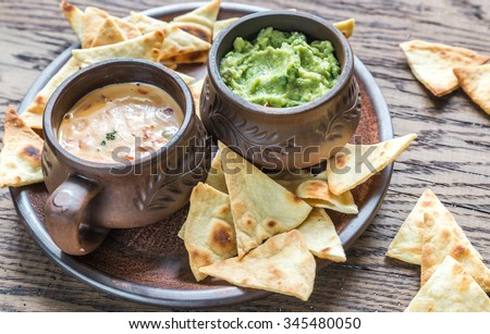 Bowls of guacamole and queso with tortilla chips - stock photo