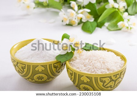 Bowls of rice and rice flour and jasmine flower - stock photo