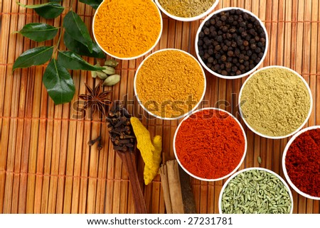 Bowls of spice powders on mat background