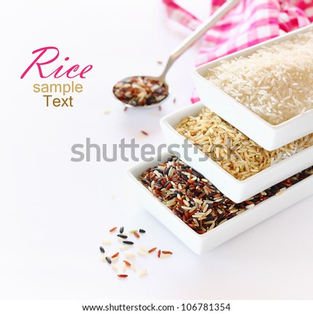 bowls of uncooked rice over white background - stock photo
