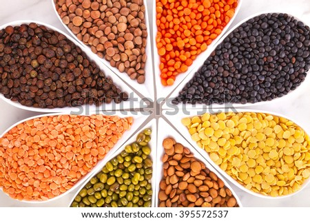 Bowls of various lentils in the shape of flower on a marble background